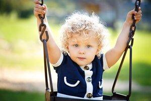 ребенок катается на качелях